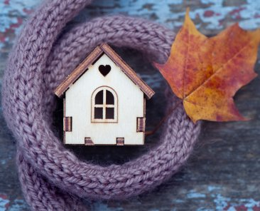 toy house is wrapped in a warm scarf with an autumn leaf. The concept is warm, cozy, loving, protecting the house. We prepare the house for the cold.
