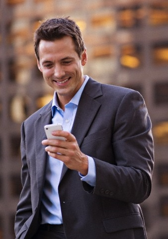 Businessman checks text messages on cell phone